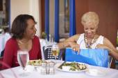 Senior African American woman opening gift bag at restaurant — Stock Photo