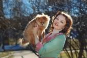 Little Pomeranian dog and pretty red haired woman playing outdoor — Foto de Stock