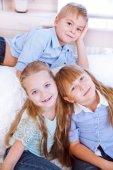 Little boy and girls sitting on the sofa — Zdjęcie stockowe