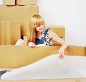 Young blond woman unpacking box.  — Stock Photo
