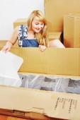 Ung blond kvinna uppackning box. — Stockfoto