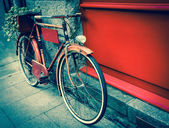 Vintage red bicycle leaning on red wooden board — Stock Photo