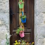 Wooden house door decorated with metal pots — Stock Photo #56095007