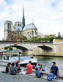 Tourists have picnic near Notre Dame Cathedral. — Stock Photo