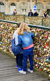 Boy and girl on Love locks bridge in Paris. — Stock Photo