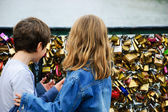 Boy and girl on Love locks bridge in Paris. — Stock Photo