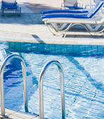 A swimming pool with sun loungers — Stock Photo