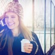 Happy teenage girl with takeaway coffee talking on smartphone — Foto Stock #61474635