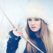 Beautiful young blonde woman with fur hat in winter — Stock Photo