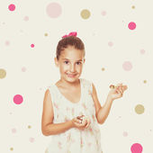 Cute little girl in floral dress eating cocoa cream — Stock Photo