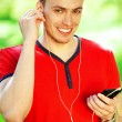 Portrait of happy young man in red t-shirt listening to music on — Stock Photo #52373751