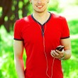 Portrait of happy young man in red t-shirt listening to music on — Stock Photo #52440385