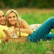 Happy moments of new family concept. Portrait of beautiful young couple having picnic in countryside — Stock Photo #58515439