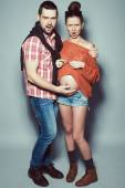 Stylish pregnancy & family concept: portrait of disturbed couple of hipsters (husband and wife) in trendy casual clothing, eyewear posing over gray background. Urban street style. Studio shot — Stock Photo
