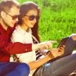 Gadget users concept. Two smiling lovers in trendy clothing and using tablet — Stock Photo #77834386