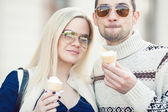 Happy fashionable pregnant couple eating ice cream in trendy clothing — Stock Photo