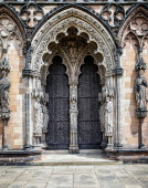 Medieval Cathedral doors surrounded by religious statues. — Stock Photo