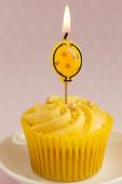 Lemon cupcake with lit balloon celabration candle — Stock Photo