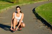 Female runner lacing sport shoes before running in park — Stock Photo