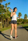 Female athlete running and waving — Stock Photo