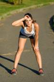 Tired female athlete taking a running break — ストック写真