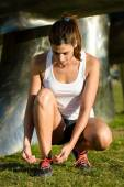 Female runner lacing sport shoes before running — Stock Photo