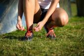 Female runner lacing sport and running shoes — Stock Photo