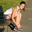 Female athlete lacing sport shoes before running in park — Stock Photo #60049715