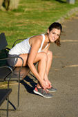 Female athlete lacing sport shoes before running in park — Stock Photo