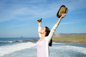 Blissful woman raising arms towards the sea — Stock Photo
