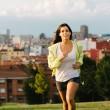 Sporty brunette woman running in city park — Stock Photo #63928749
