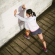 Asian athlete stretching legs before running — Stock Photo #66063485