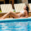 Relaxed woman tanning at resort swimming pool — Stock Photo #66073837