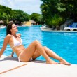 Young woman sunbathing and relaxing at resort swimming pool — Stock Photo #66073959