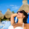 Woman on relaxing vacation at tropical resort beach sunbathing — Stock Photo #69141121