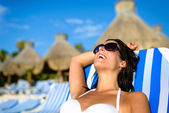 Woman on relaxing vacation at tropical resort beach sunbathing — Stock Photo