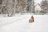 Six year old girl playing with vintage sleds in winter — Photo