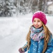 Portrait of a cute little girl with long blond hair, dressed in a blue coat and a pink hat in the winter forest — Stock Photo #62520745