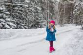 Six year old girl in a blue coat and a pink hat and boots grimacing in the winter forest — Стоковое фото