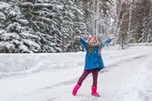 Girl dressed in a blue coat and a pink hat and boots throws snow up — Stock Photo