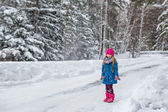 Little Girl dressed in a blue coat and a pink hat and boots throws snow and laughs — Stock Photo