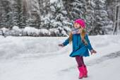 Little girl dressed in a blue coat and a pink hat and boots, fun runs through the winter forest — Stock Photo