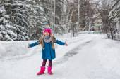 Little girl dressed in a blue coat and a pink hat and boots, hamming and playing in the winter forest — Stock Photo