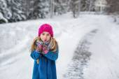 Cute little girl in a pink hat and blue coat freezing in winter — Stock Photo
