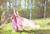 Beautiful blonde girl in a pink dress on a long evolving nature background — Stock Photo