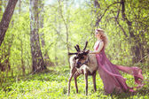Girl in fairy dress with a flowing train on the dress and reindeer in the forest — Stock Photo