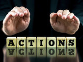 Hands Over Letter Tiles Spelling the Word Actions — Stock Photo