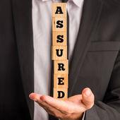 Businessman Holding Letter Blocks Spelling Assured — Stock Photo