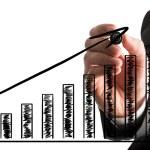 Businessman drawing an ascending bar graph — Stock Photo #57490969