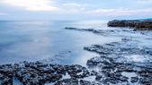 Rocky seashore and calm blue ocean — Stock Photo